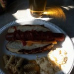 A hot dog, pasta salad and some potato salad